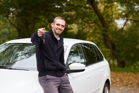 Handsome man with the key standing in front of car Stock Photo
