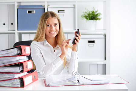 payroll: Smiling business woman calculates tax at desk in office