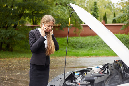 car trouble: Young woman with a broken car calling for assistance