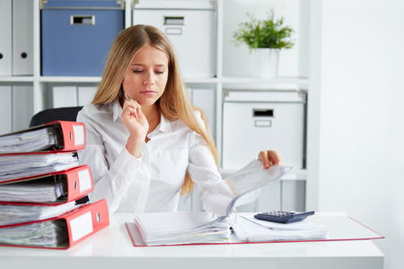 Hermosa mujer de negocios determina el impuesto en el escritorio en la oficina Foto de archivo