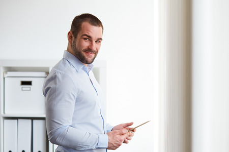 Young man with a tablet in his hands and smiling into the camera Stock Photo