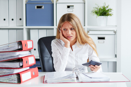 Pensive business woman calculates taxes at desk in office