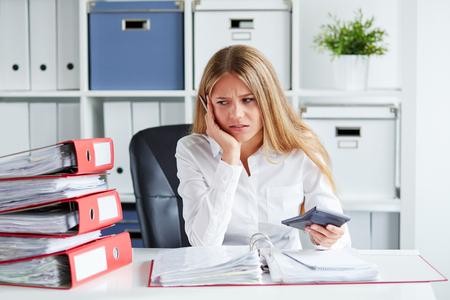 impuestos: Mujer de negocios pensativa calcula los impuestos en el escritorio en la oficina