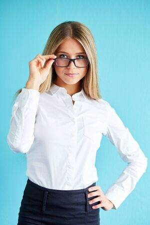 blue shirt: Businesswoman in white shirt with glasses, standing over blue background. Stock Photo