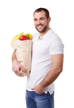 healthy men: Young man holding paper bag full of vegetables, on white background Stock Photo