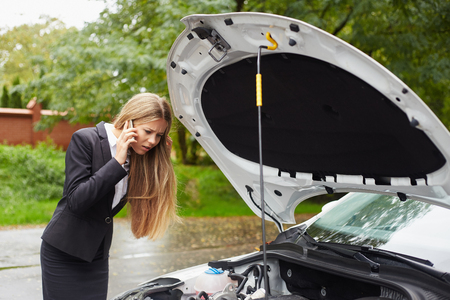car mechanic: Business woman with a broken car calling for assistance