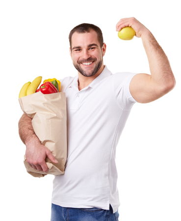 apple paper bag: Man holding paper bag full of vegetables and in his other hand apple, on white background Stock Photo