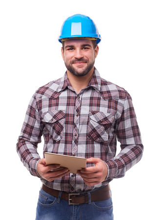Manual worker in blue helmet and shirt using a digital tablet, isolated on white.