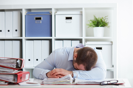 Tired young businessman sleeping in the office