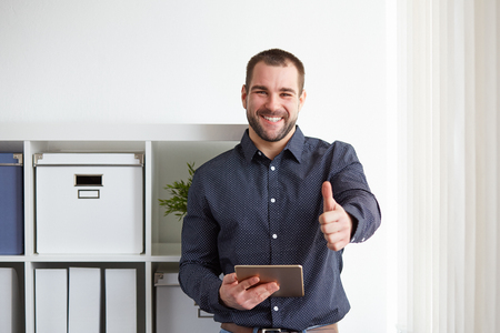 Happy businessman with digital tablet makes a gesture thumb up in the office Foto de archivo