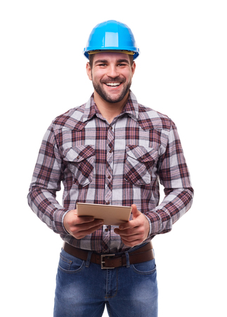 Happy manual worker in blue helmet and shirt using a digital tablet, isolated on white.