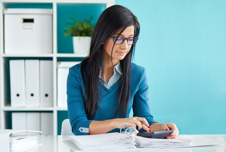 Beautiful business woman calculates tax at desk in office