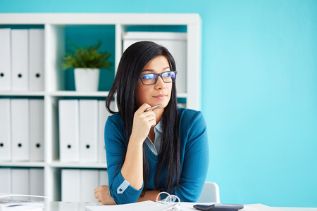 looking out: Beautiful business woman sitting in office and looking out the window Stock Photo