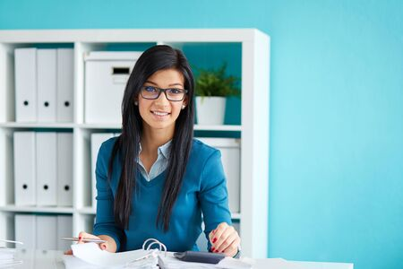 Happy businesswoman with glasses calculates tax at desk in office
