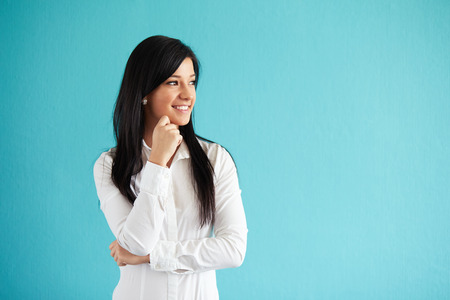 white woman: Beautiful woman in white shirt standing against a blue wall