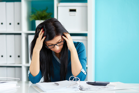 stressed: Young business woman under stress with head in hands