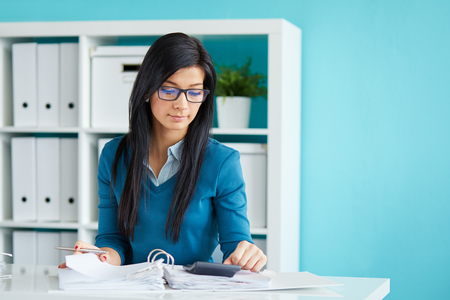 impuestos: Young businesswoman with glasses calculates tax at desk in office