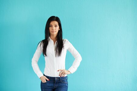 blue wall: Beautiful woman standing in front of turquoise wall