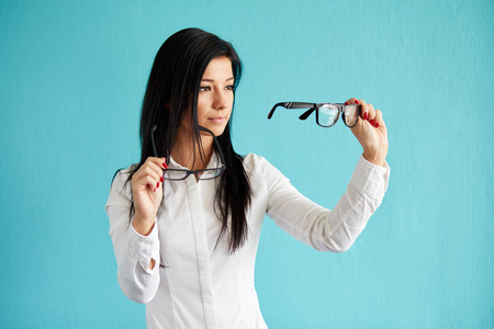 decides: Pensive woman with glasses standing before blue background Stock Photo