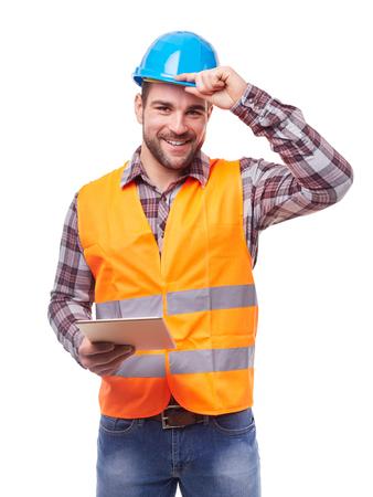 Trabajador manual en el casco azul con la tableta digital, aislado en blanco.