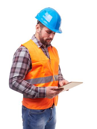 Robotnik w kasku niebieskim i koszulę przy użyciu cyfrowego tabletu, wyizolowany na białym tle.