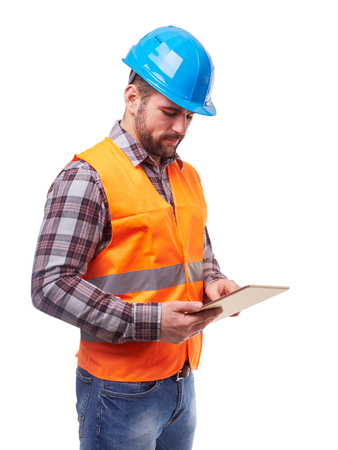 Trabajador manual en el casco azul y camisa usando una tableta digital, aislado en blanco.