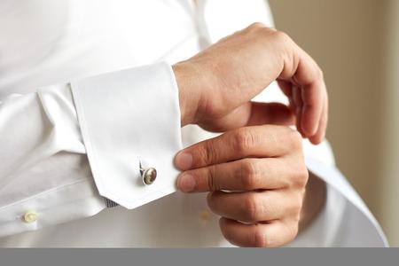 Man correcting the sleeve of his shirt, close up