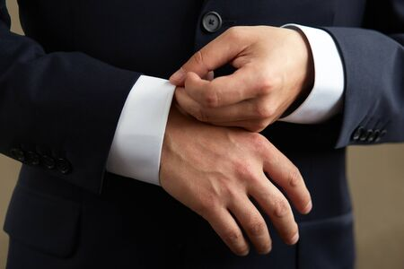 his shirt sleeves: Man in black suit, correcting the sleeves of his shirt, close up