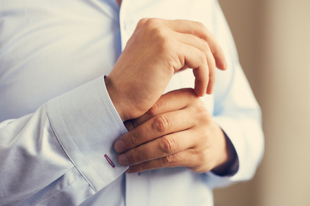 tailored: Man correcting the sleeve of his shirt, close up. Toned
