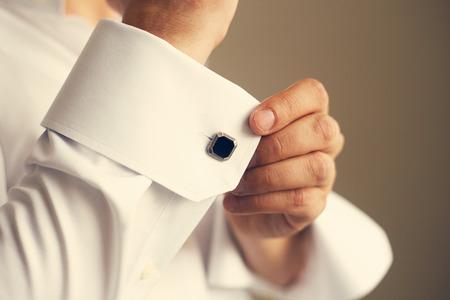 그의 셔츠의 소매를 수정하는 남자를 닫습니다. 톤 스톡 콘텐츠 - 59199127