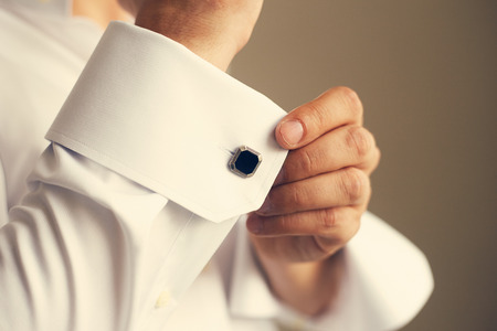 Man correcting the sleeve of his shirt, close up. Toned