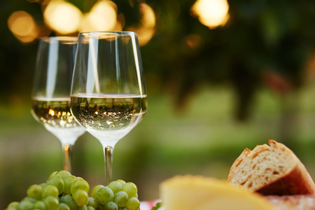 Two glasses of white wine with food at sunset 스톡 콘텐츠