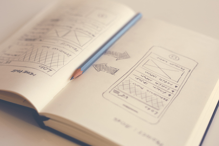 Pencil lying on an open diary with a sketch web design. Toned 스톡 콘텐츠
