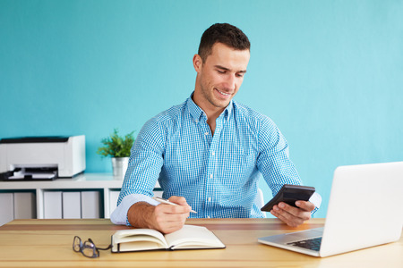 Smiling businessman calculates tax at desk in office 스톡 콘텐츠