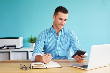 Smiling businessman calculates tax at desk in office Foto de archivo