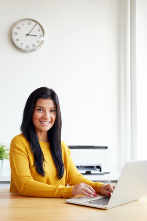 working at home: Portrait of smiling woman sitting at her desk working with laptop in the home office