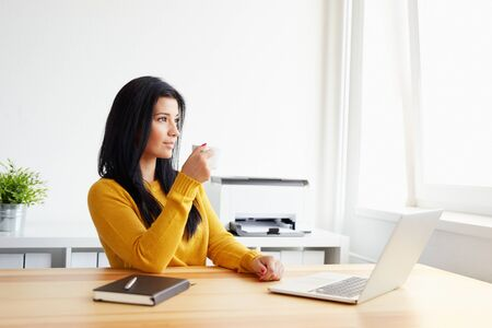 looking at computer: Young woman drinking coffee in the office