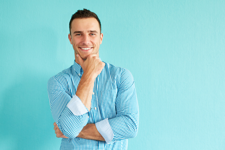 Smiling pensive man in front of turquoise wall