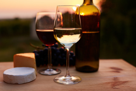 wine glasses: Low key image, two glasses of wine with cheese on table, toned at sunset. Stock Photo