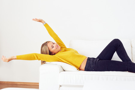 woman on couch: Beautiful woman stretching on a couch in the living room Stock Photo