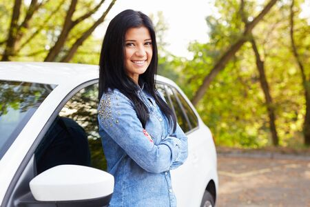 leaning: Happy woman with crossed arms standing by her car