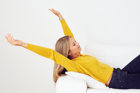 woman on couch: Young woman stretching on a couch in the living room Stock Photo