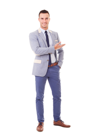 young businessman: Smiling man in blue jacket showing empty copyspace, isolated on white background