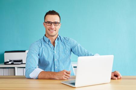 usando computadora: Sonriente hombre de trabajo en la oficina moderna en el ordenador