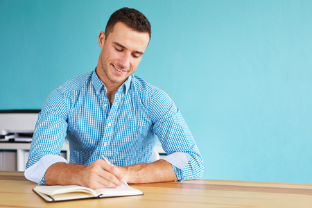 Young happy man sitting in his office and writing plan in his diary Stock Photo