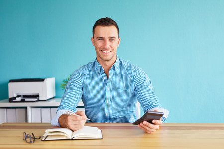 Happy businessman calculates tax at desk in office