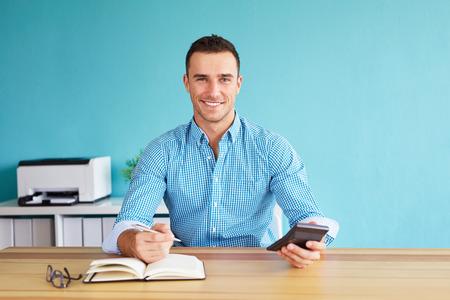 Uomo d'affari felice calcola la tassa alla scrivania in carica Archivio Fotografico