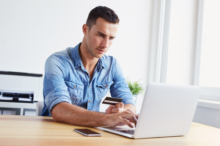 Man sitting in his office holding credit card and using laptop