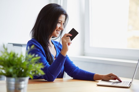 credit cards: Young woman paying with a credit card on the notebook Stock Photo