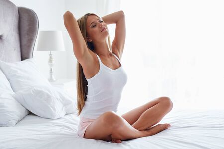 pretty young girl: Beautiful woman stretching in her bed after wake up in the bedroom Stock Photo